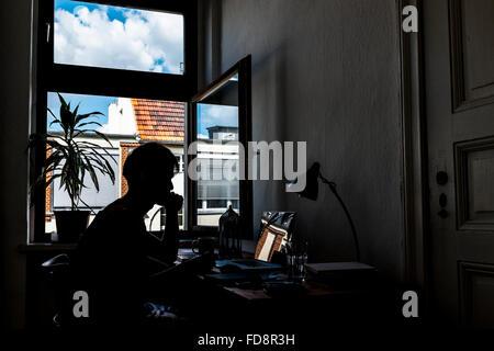 Silueta de hombre utilizando un portátil en una mesa