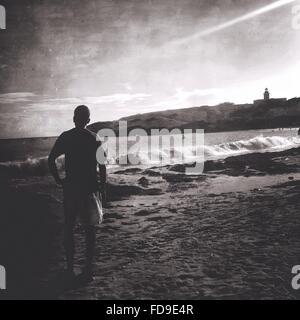 Vista trasera del joven parado en la playa