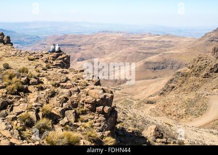 Dos personas sentadas en el borde de un acantilado mirando por encima de las montañas de Lesotho, África