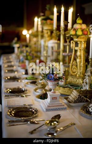 Mesa de comedor y candelabros con arreglos florales y la vajilla en el Comedor de Attingham Park, Shrewsbury, Shropshire.