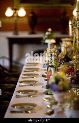 Cerrar la vista de la mesa del comedor con platería y decoración floral, y el período de alimentos en detalles de Attingham Park, Shrewsbury, Shropshire.