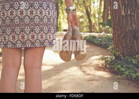 Vista trasera de una mujer sosteniendo par de zapatos.