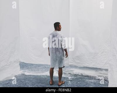 Vista trasera de la longitud completa de hombre de pie contra la pared blanca