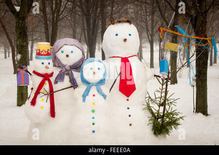 Familia de cuatro muñecos de nieve en invierno al aire libre