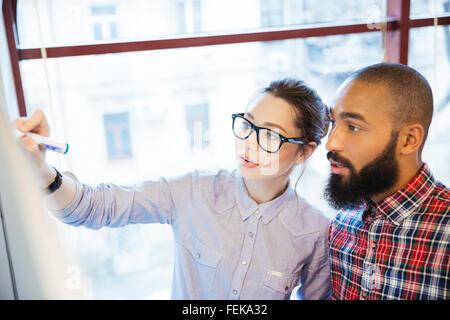 Jóvenes empresarios que trabajan con pizarra en Office