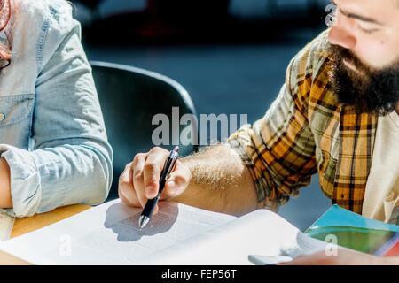 Captura recortada del macho y de la hembra y estudiantes universitarios en la mesa de lectura Foto de stock