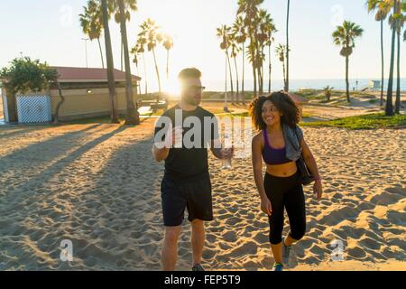 Par vistiendo ropa deportiva, caminar por la playa, hablando Foto de stock