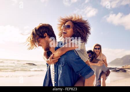 Grupo de amigos caminando por la playa, con los hombres que piggyback ride para novias. Feliz jóvenes amigos disfrutando de un día en b