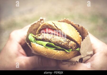 Primer plano de manos sosteniendo la hamburguesa