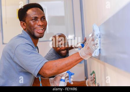 Un equipo de limpieza profesional matorrales, spray y limpie todas las superficies en salas de hospital. Crédito: Euan Cherry