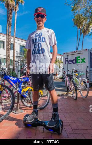 Un adolescente masculino se detiene y detiene su paseo en su hoverboard en una acera en Santa Barbara, California, con gafas de sol. Foto de stock