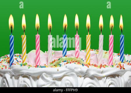 Tarta de Cumpleaños con coloridas velas en el fondo verde.