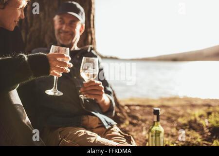 Close Up retrato de pareja senior bebiendo vino mientras camping cerca de un lago. Se centran en manos sosteniendo una copa de vino.