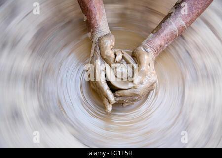 La cerámica , artista manos embarradas hacer una vasija de barro para dar forma a la rueda que patina, la aldea semi urbanas Dilwara , Udaipur Rajasthan