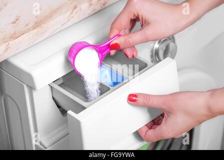 Mujer lanza servicio de lavandería detergente en la lavadora.
