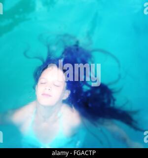 Un alto ángulo de visualización de la mujer joven con los ojos cerrados en la piscina