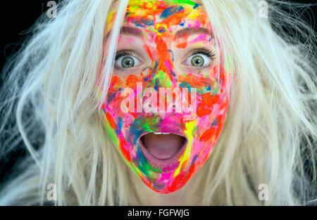 Mujer con cabello rubio desordenado y el rostro cubierto de pintura multicolor con una expresión de sorpresa