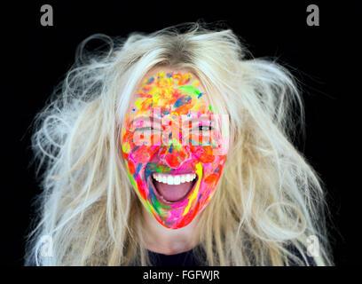 Mujer con cabello rubio desordenado con el rostro cubierto de pintura multicolor riendo