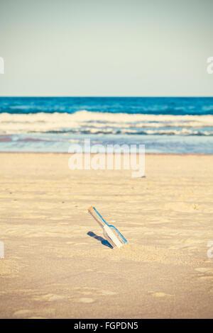 Cruz foto procesada de una botella con la carta sobre la playa, poca profundidad de campo.