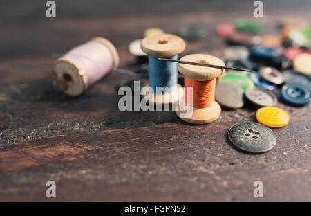Carretes de hilos y botones en la mesa de madera antigua