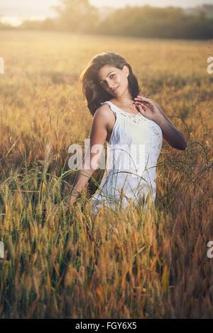 Retrato de una mujer hermosa en un campo. Luz del atardecer de verano
