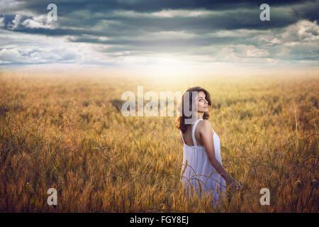 Bella mujer en un campo de maíz con dramáticas sky . Luz del atardecer