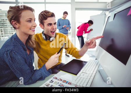 Diseñador gráfico usando audífonos en el escritorio