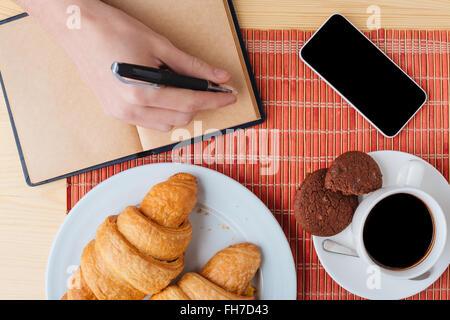 Vista superior de la tabla con el desayuno, teléfono celular y portátil