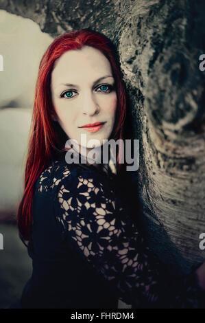 Retrato de la mujer de pelo rojo por el árbol