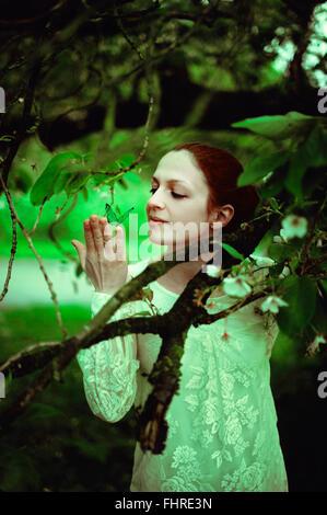 Joven en el bosque sosteniendo una mariposa