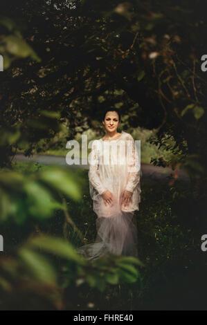 Joven mujer vistiendo vestido blanco de pie en el bosque
