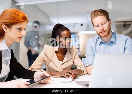 Grupo de hombres de negocios sentados frente al escritorio y tener una reunión sobre estrategia futura