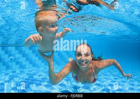 Lección de natación infantil - Baby Boy con la madre aprender a bucear bajo el agua en la piscina con aguas cristalinas.