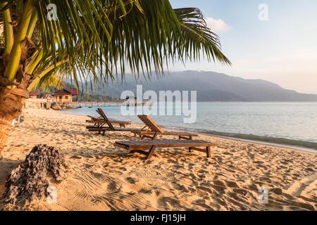Sillas sobre una larga playa en Pulau Tioman, Malasia Foto de stock