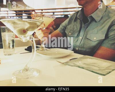 La mitad del torso de hombre con bebida en una mesa en el restaurante