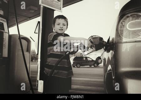 Retrato de niño con la bomba de combustible en la Gasolinera