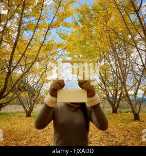 Primer plano de la mujer sosteniendo la imagen de los árboles en la parte delantera de la cara