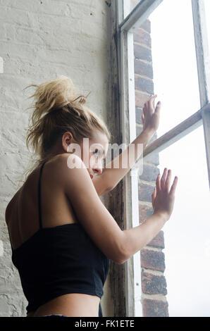 Asustada mujer mirando por la ventana