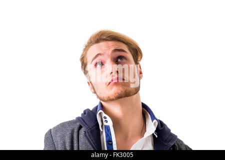 Joven atractivo pensando, mirando hacia arriba con la mano en la barbilla, aislado sobre fondo blanco, con expresión dudosa Foto de stock