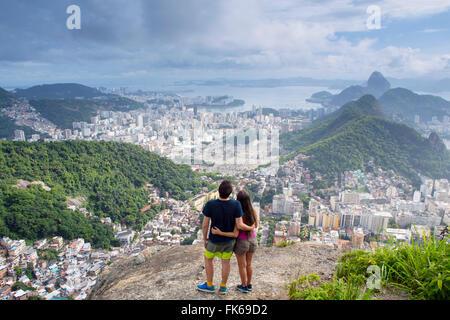 Excursionistas mirando a lo largo de Río de Janeiro desde el Morro dos cabritos hill, Río de Janeiro, Brasil, América del Sur