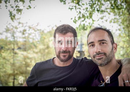 Una pareja gay caucásico abrazando al aire libre