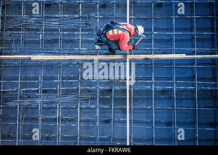 Trabajador caucásico clavando tablones en sitio en construcción