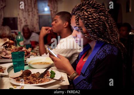 Adolescente mediante celular en la mesa