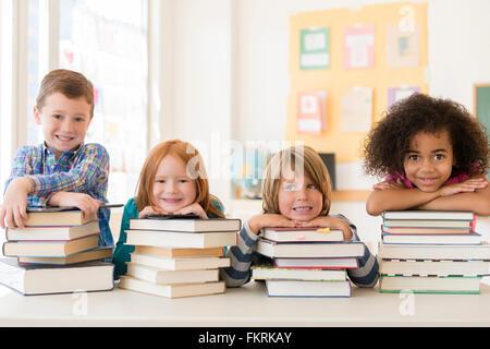 Los estudiantes descansando sobre pilas de libros en el aula