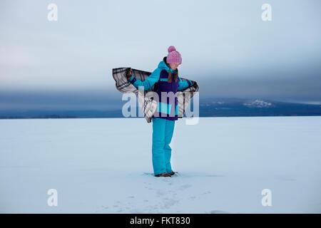 Caucasian adolescente envuelto en una manta en la nieve