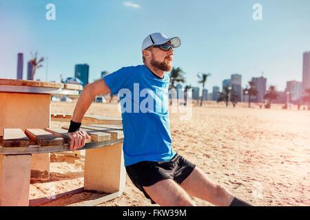 Mitad hombre adulto en la playa haciendo marcha atrás empujar hacia arriba sobre un banco, Dubai, Emiratos Árabes Unidos.