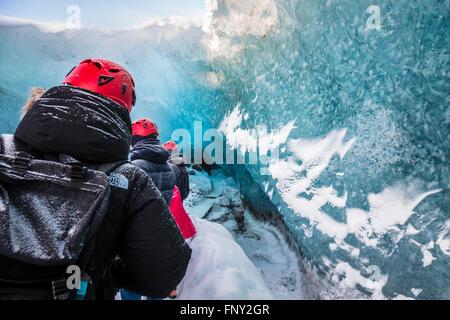 La gente en la entrada de una cueva de hielo, Parque Nacional, el glaciar de Vatnajökull, Islandia