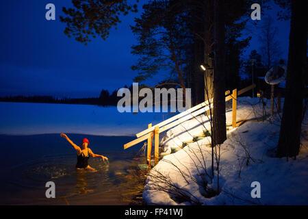 La gente toma un sauna en una cabaña junto al río Kemi, Salla, Laponia, Finlandia. Impresionante experiencia de sauna. Una Saun finlandés