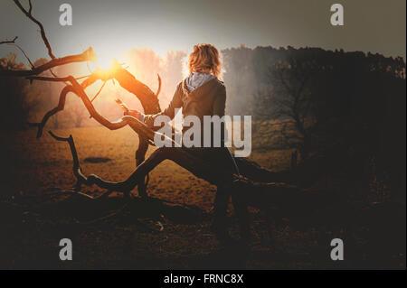 Mujer joven apoyado sobre un árbol caído en Sunset Park