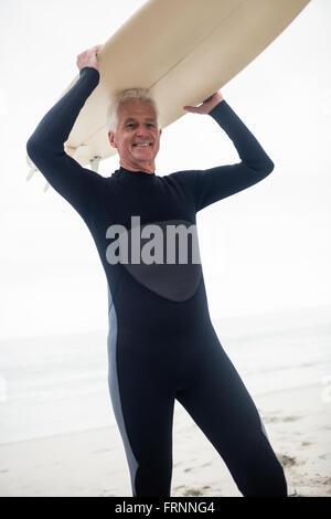 Retrato de altos hombre sujetando una tabla de surf sobre su cabeza
